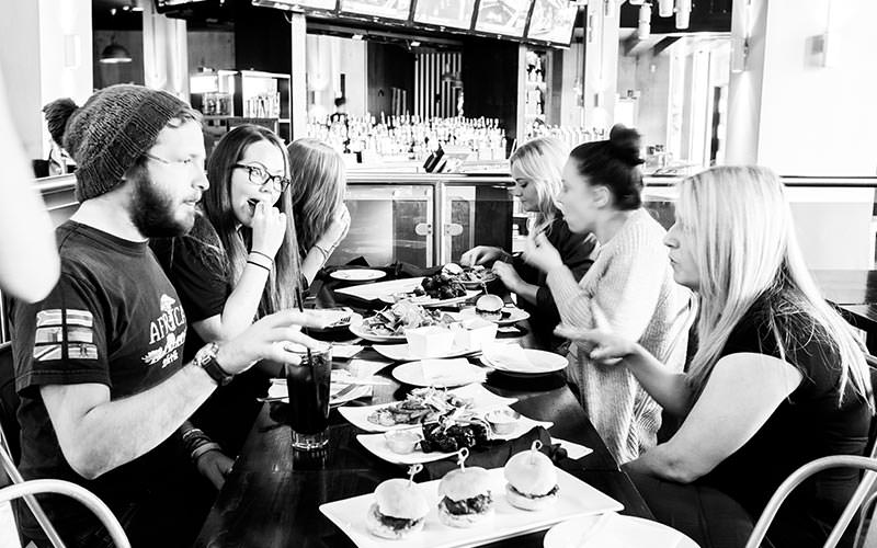 A black and white image of lots of people eating food at a table