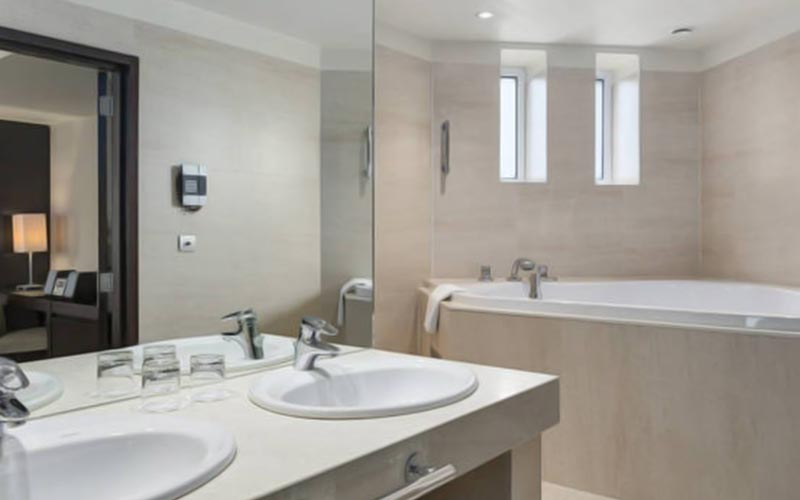 The bathroom area with large bath and double sink