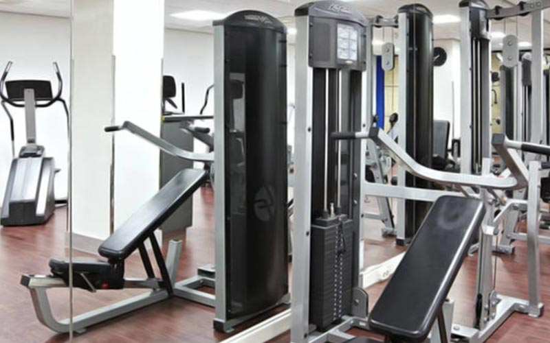 A gym area with lots of fitness equipment