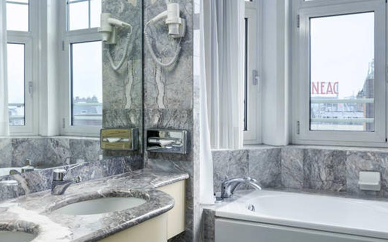A bathroom with marble surfaces and a bath under the window