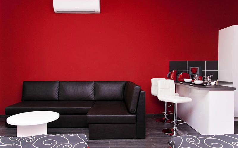 A black leather sofa in Krisco II Apartments with red walls and bar stools