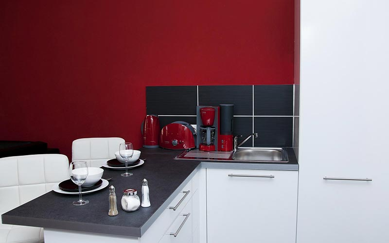 The kitchen area in Krisco II Apartments with red walls and white cupboards
