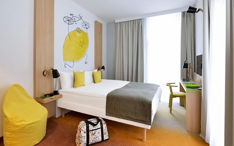 A twin room in Ibis Styles Budapest City with a bag on the floor and a lemon and grey colour scheme