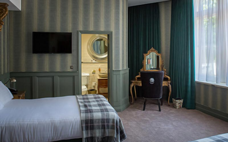 A double room within The Exchange, with vintage striped wall paper and bathroom door open leaving bathroom visible