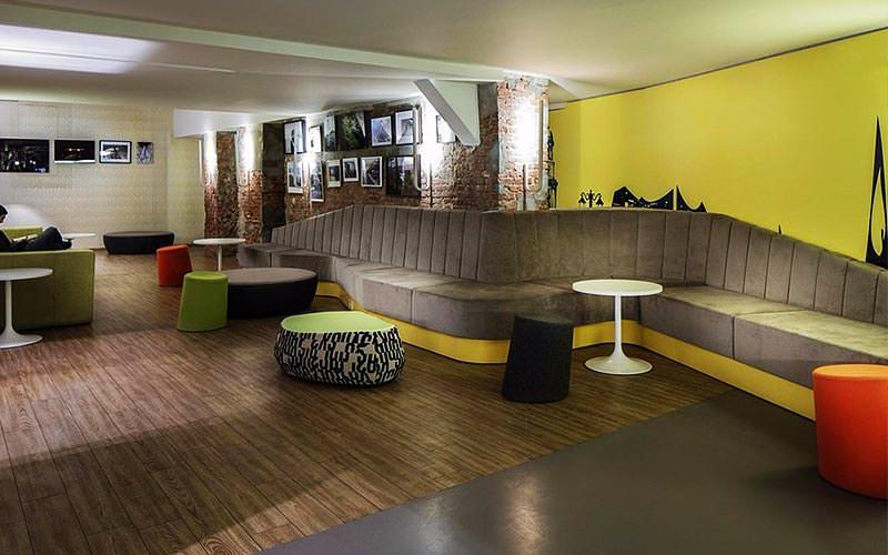 Various stools and seating along the wall in a room at Generator Hamburg