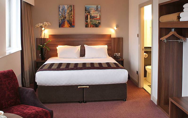 A large double bed in a dark hotel room, with a closet and bathroom in the side