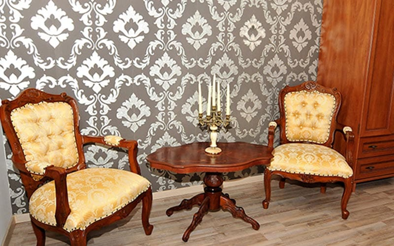 Two vintage chairs in Old City Hotel with paisley wallpaper behind them