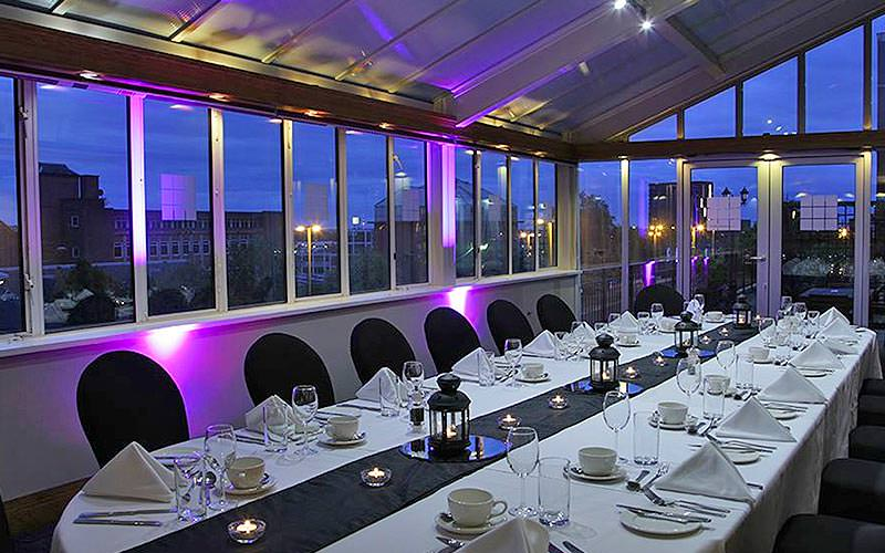A long table set up for dinner in a glass hotel restaurant, to a backdrop of purple light