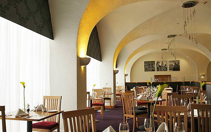 Tables and chairs set up for dinner in an arched restaurant