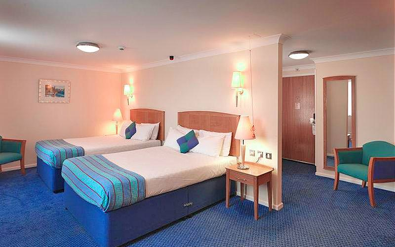 Two double beds in a blue hotel room, with a chair in the corner