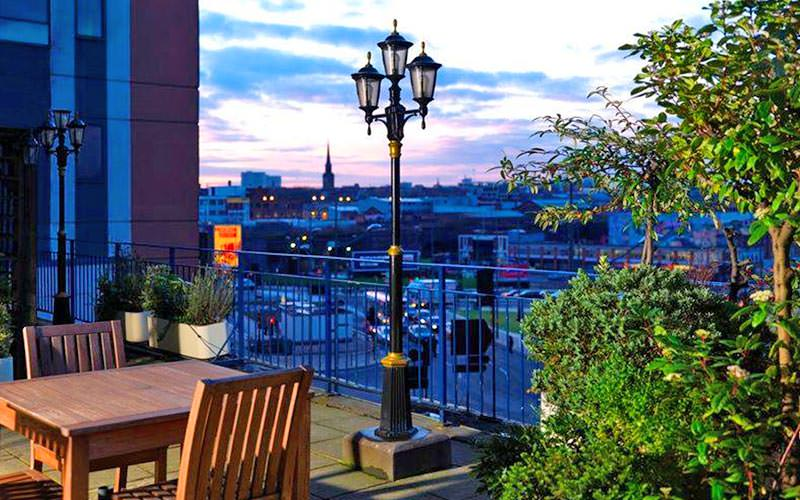 Table and two chairs on an outdoor terrace, with a building skyline in the background