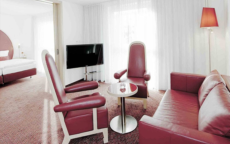 A red sofa and seats in a hotel room