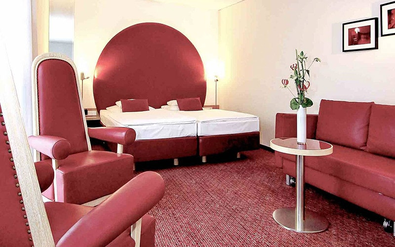 A red themed hotel room with seating and beds all red