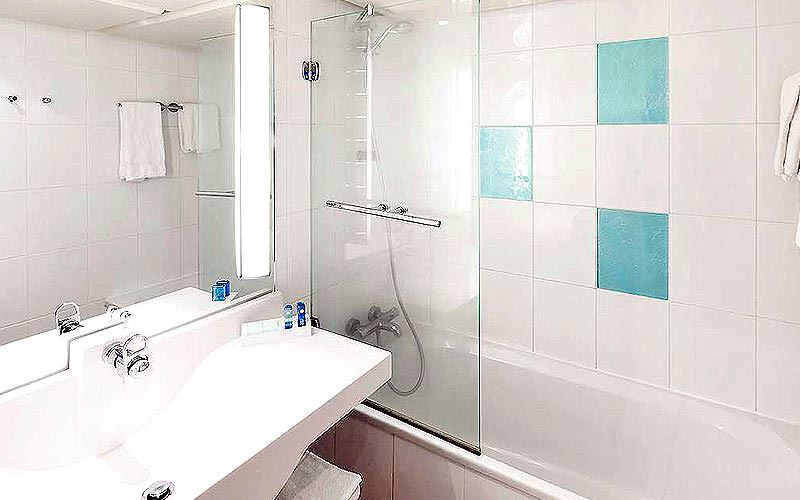 Clean white bathroom with over bath shower and modern sink. Hotel bathroom.