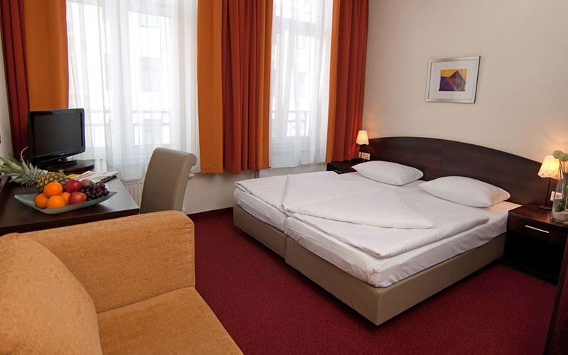 A double room in Novum Hotel Eleazar City Centre with a red carpet and orange curtains