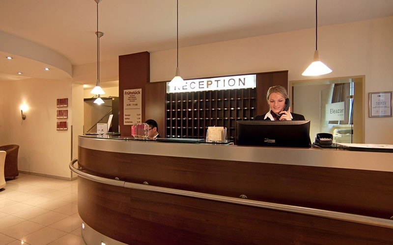 The reception area of Novum Hotel Eleazar City Centre with a woman on the phone at the desk