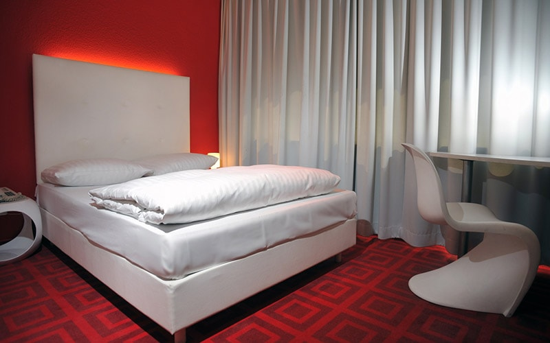 A double bed with white bedding in a red room with red walls and carpets