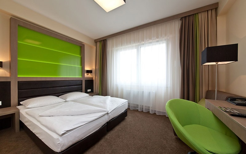 A double room with a white and lime green colour scheme