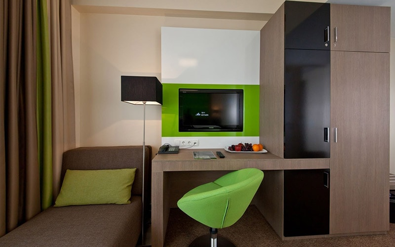 A room with a TV on the desk and a lime green colour scheme