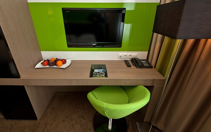 A desk with a lime green seat at it and a TV mounted in the wall