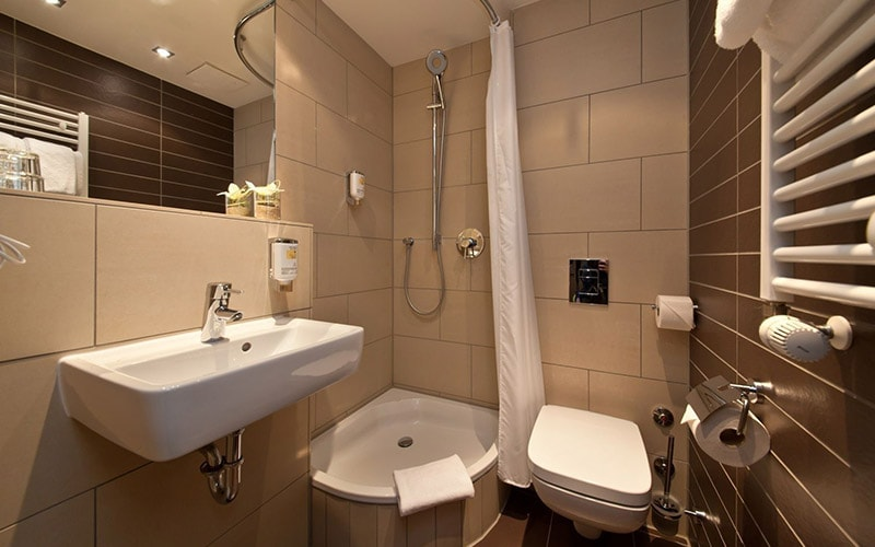 A white bathroom with cream tiles on the wall