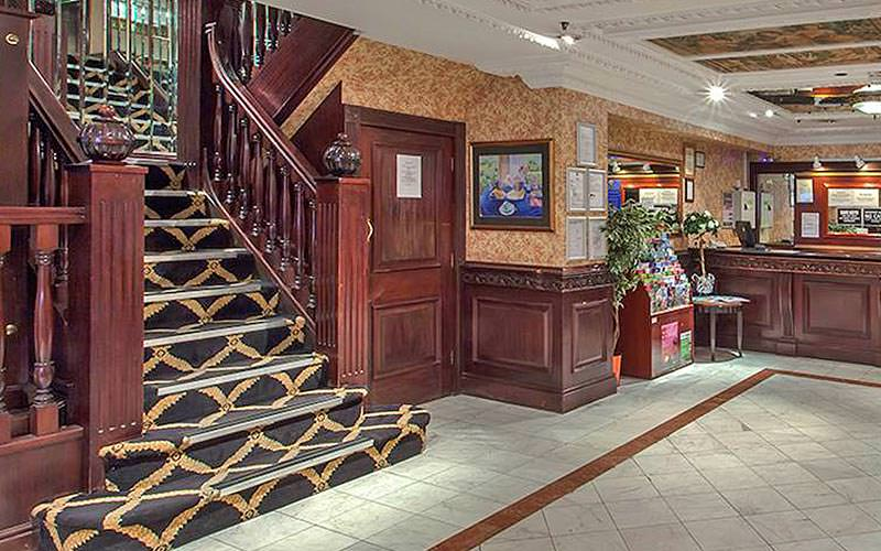 The reception area of Britannia Hotel with a plush staircase and reception desk