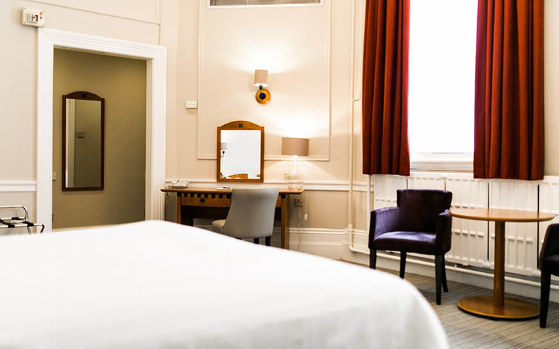 The edge of a double bed and a dressing table and desk in The Angel Hotel