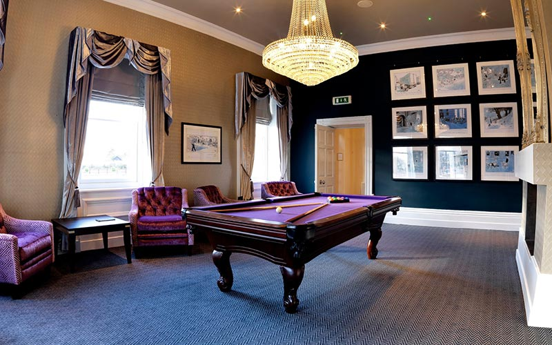 A room with a pool table in the middle