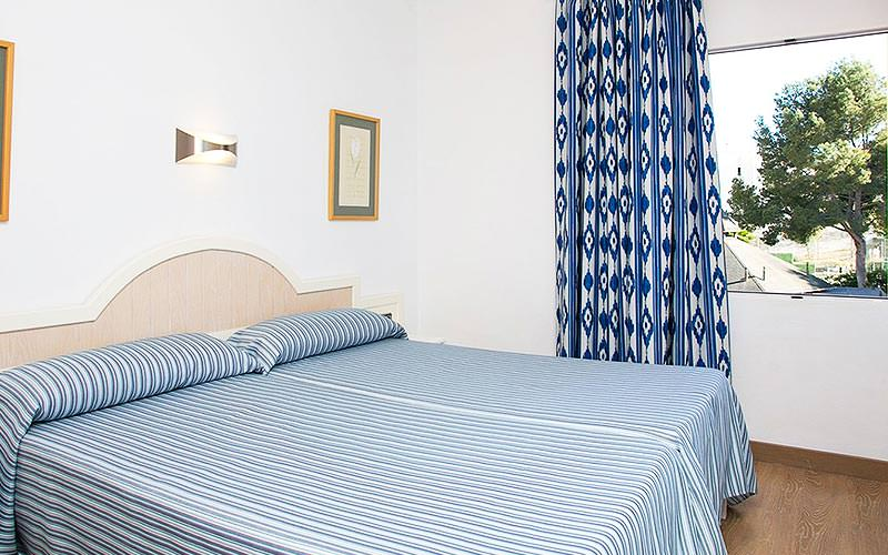 A double bed with striped blue bedding, with a blue curtain on the window in the background