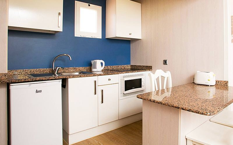 A white kitchenette with a breakfast bar