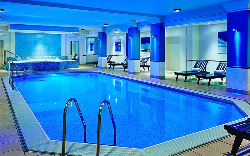 Indoor swimming pool and Jacuzzi, with sun loungers along the side