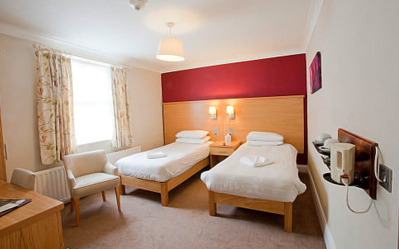A twin room with a large window and red and white walls