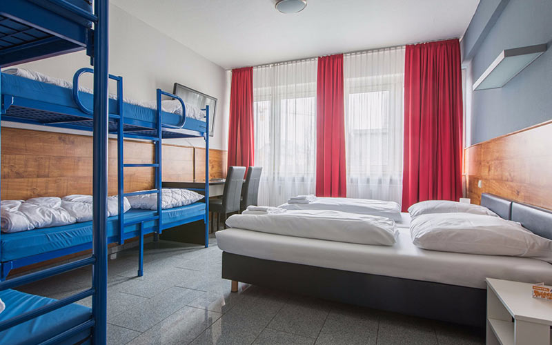 A room with red curtains and a window, with single beds and bunk beds inside it