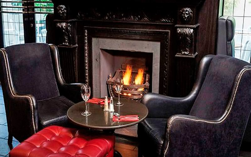 A cosy fireplace with two plush seats and wine glasses on the table