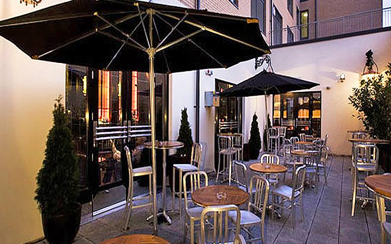 The outdoor terrace seating area with black parasol umbrellas out