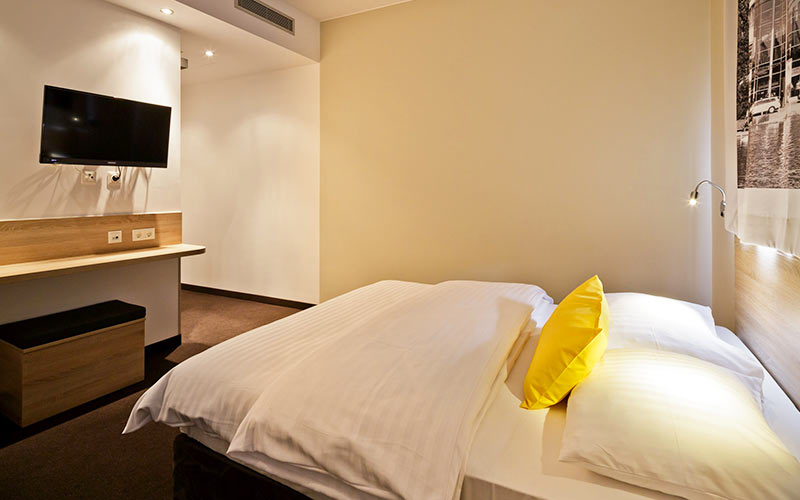A hotel room with a bed and TV