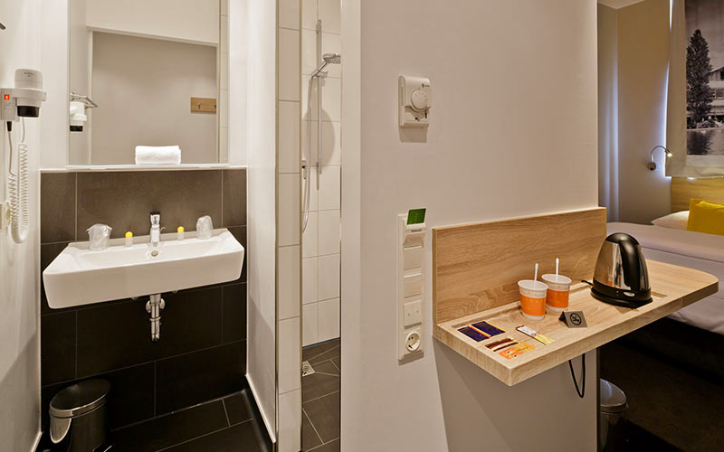 A bathroom sink and a shelf with tea and coffee making facilities