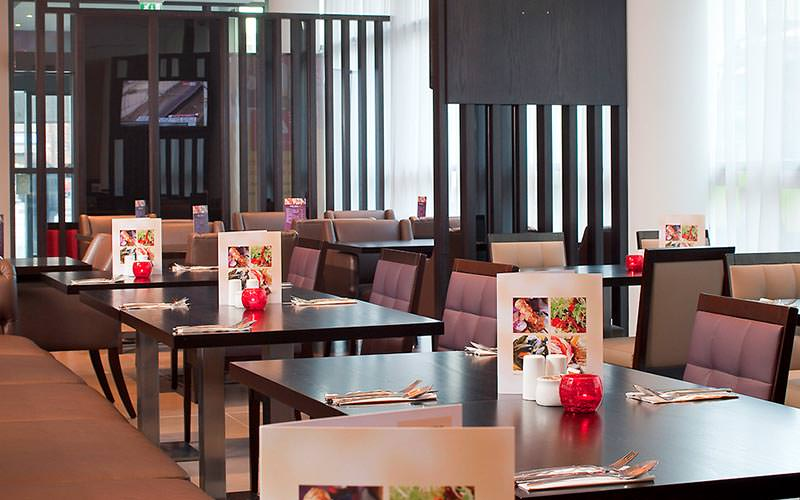 Tables and chairs set up for dinner in the hotel restaurant at Ibis Belfast City Centre
