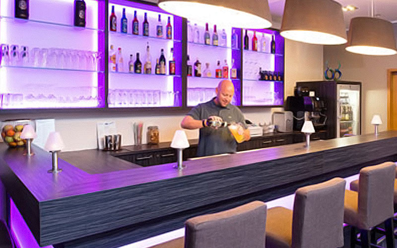 A purple lit bar with someone pouring a drink