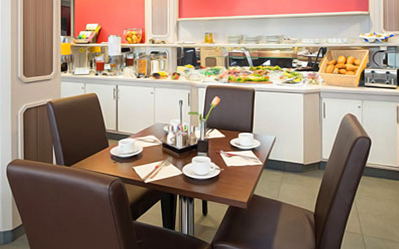 A table and chairs with a selection of food in the background