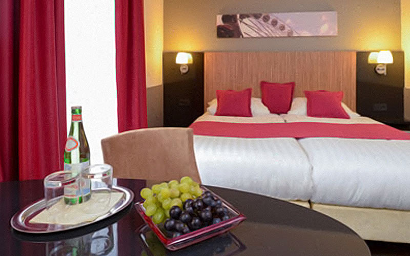 A double bed and a table in the foreground with some grapes on