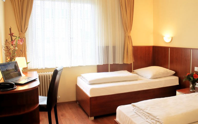A hotel room with two single beds and a desk with a laptop on