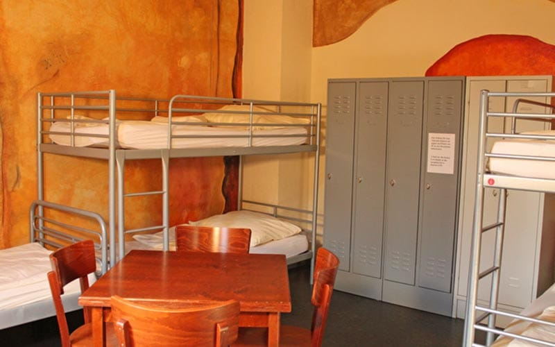 Close up of two bunk beds with a single bed with lockers and a table in the middle with four chairs
