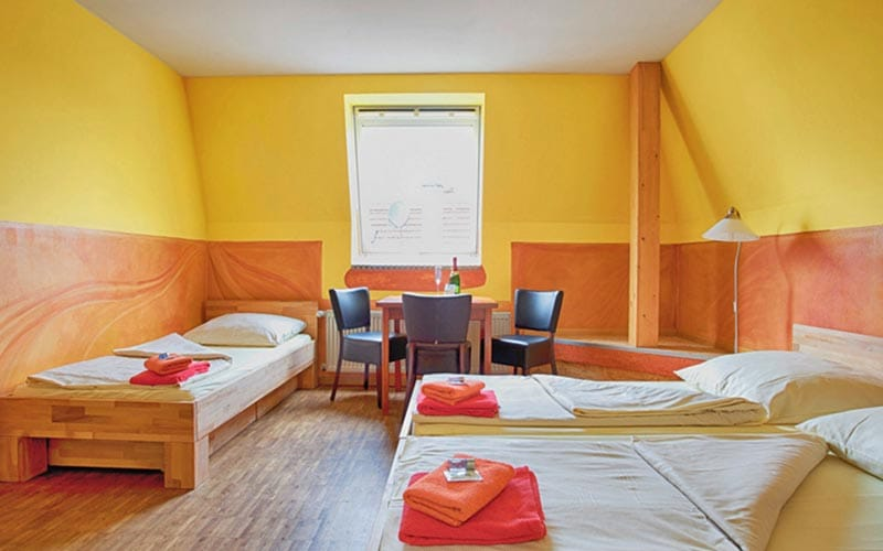 Big yellow and orange room with three single beds and table and three chairs next to the window