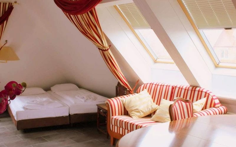 Attic room with two windows a striped sofa and two single beds pushed together