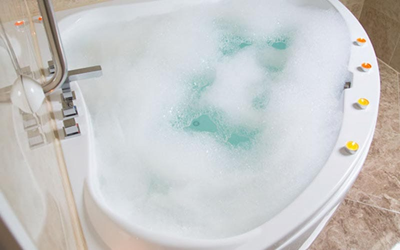 Close up of corner shaped bath filled with bubbles