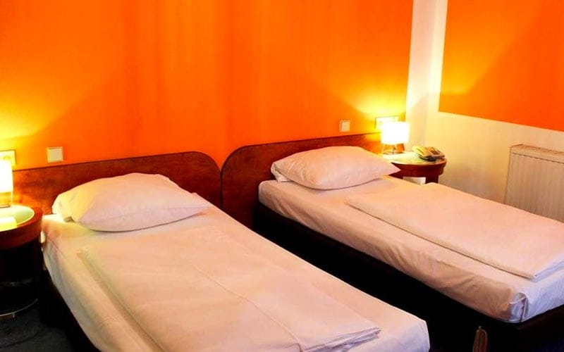 Close up of two single beds with orange walls