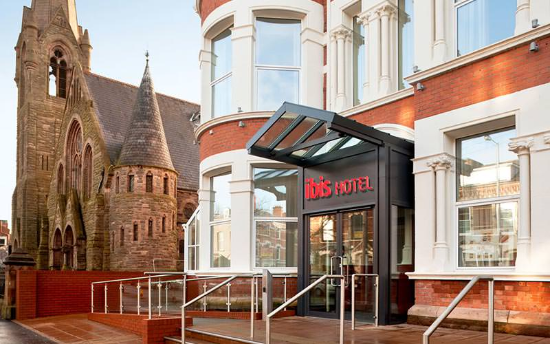 The entrance to Ibis Belfast Queens Quarter, with a grand cathedral in the background
