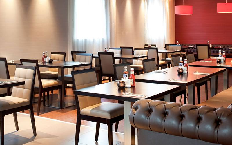 Tables and chairs set up for dinner in the Ibis Belfast Queens Quarter hotel restaurant