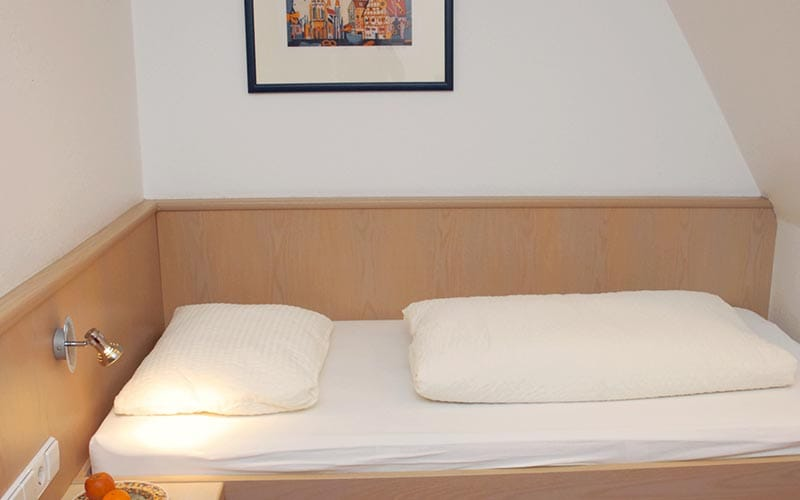 A small single bed with a bedside lamp on